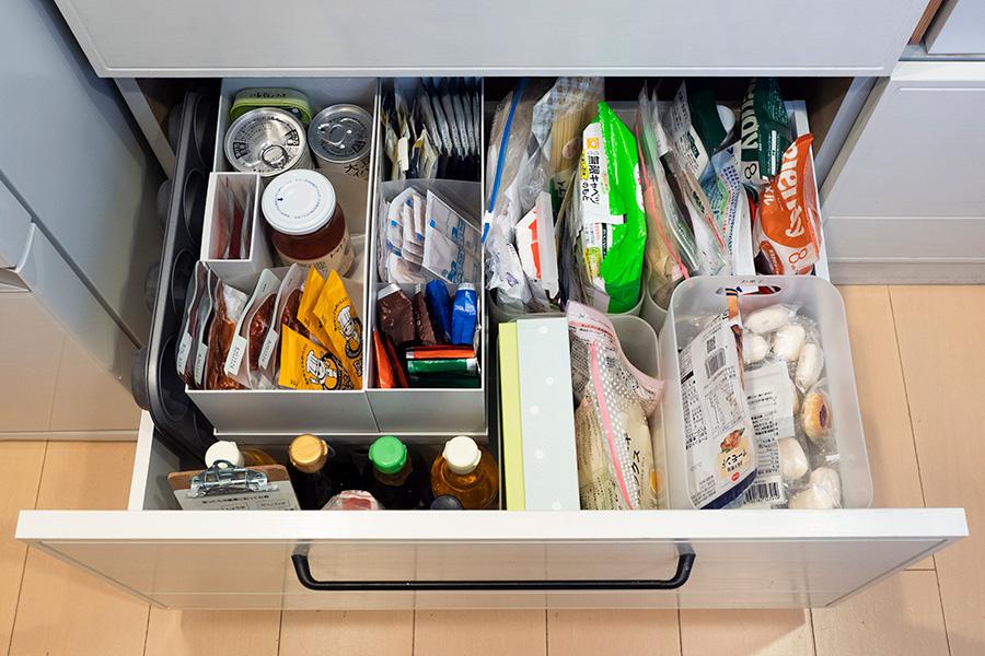 食品のストックコーナー。あまり使わないお弁当箱を収めたフタ付きのファイルボックスの上に、さらにボックスを重ねて収納力を高めた。