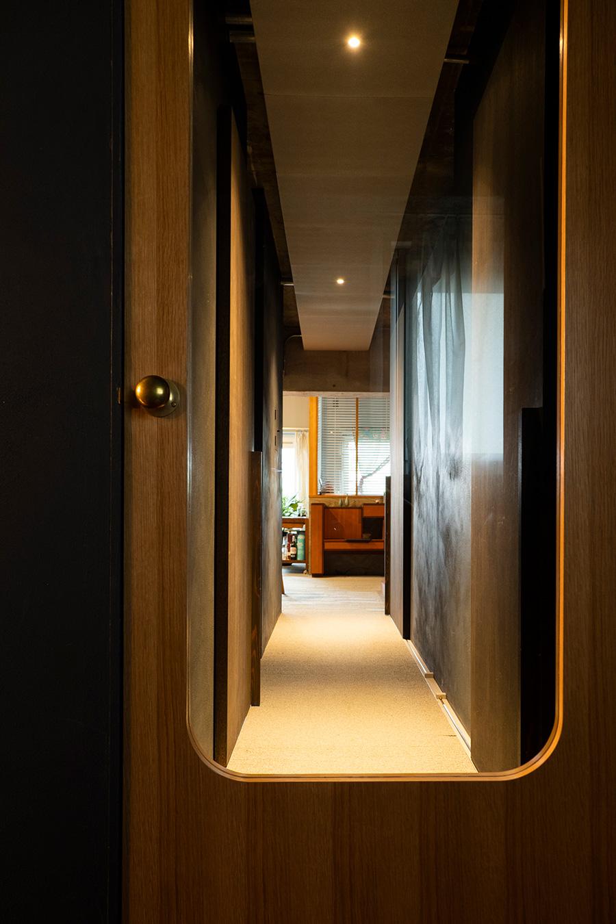 玄関と室内を仕切るドア。ガラスと真鍮の取っ手を用いた。