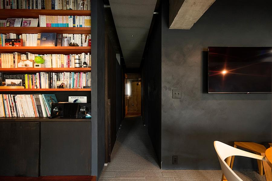 暗い廊下の向こうに玄関の灯りがほんのりと。壁を黒く塗装するのは夫婦揃っての希望だった。