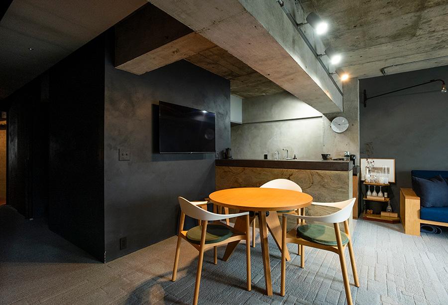 ジャン・プルーヴェがデザインしたVitra社のダイニングテーブルGUERIDONに、イスはイタリアのインテリアブランドPlankのMonzaチェア。梁を活かして設置したスポットライトは気分に合わせて調色することができる。