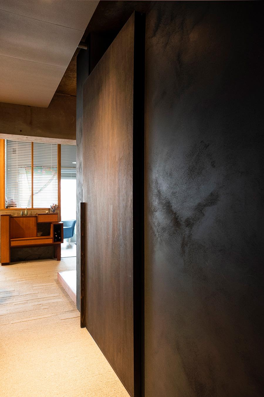 ムラのある黒い塗装が光を反射。天井の吸音材には、遮音に加え配管を隠す目的が。