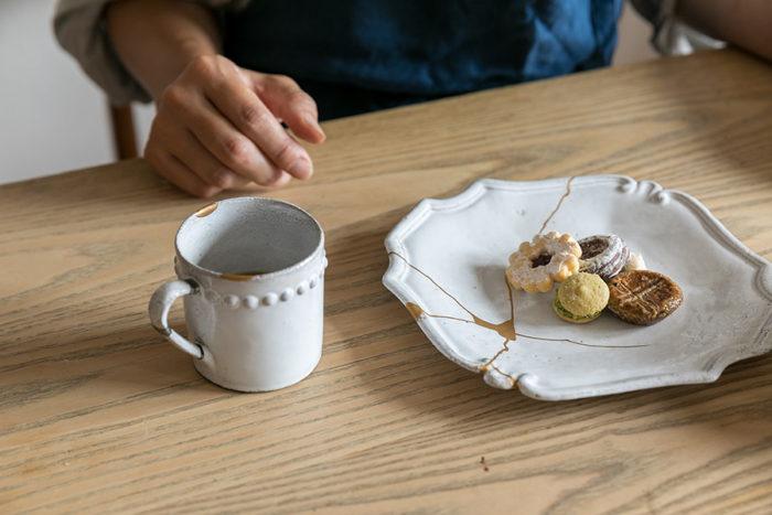 アスティエの器は不思議と金以外にもいろいろな色が似合う。左のカップは、飲み口のカケに金を、持ち手にプラチナ粉を蒔いている。
