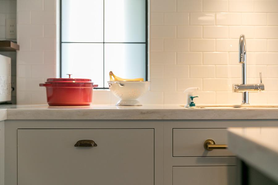 既存の窓の手前に格子の曇ガラス入れて二重窓にすることで、海外の家を思わせるキッチンに。カウンターの下に食洗機やゴミ箱などをすっきりと収めた。「子どもがいたずらしにくいのもありがたいです」