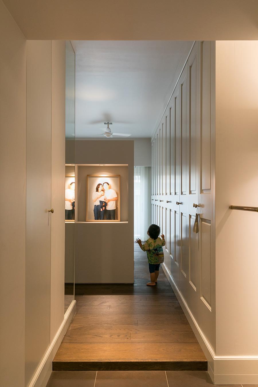 玄関ドアを開けると、右側に連続した収納。年賀状のためにスタジオで撮影した家族写真が飾られた棚は、グルリと回遊できる。一生くんがグルグル走って遊ぶのだとか。
