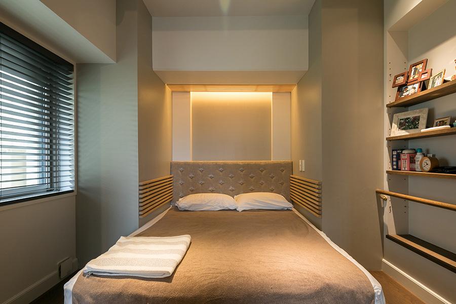 既存の壁にスッポリと収めたベッドは、不思議な安心感があるのだとか。背もたれはクッション素材に。手前に子供部屋へと続くウォークスルークローゼットがある。
