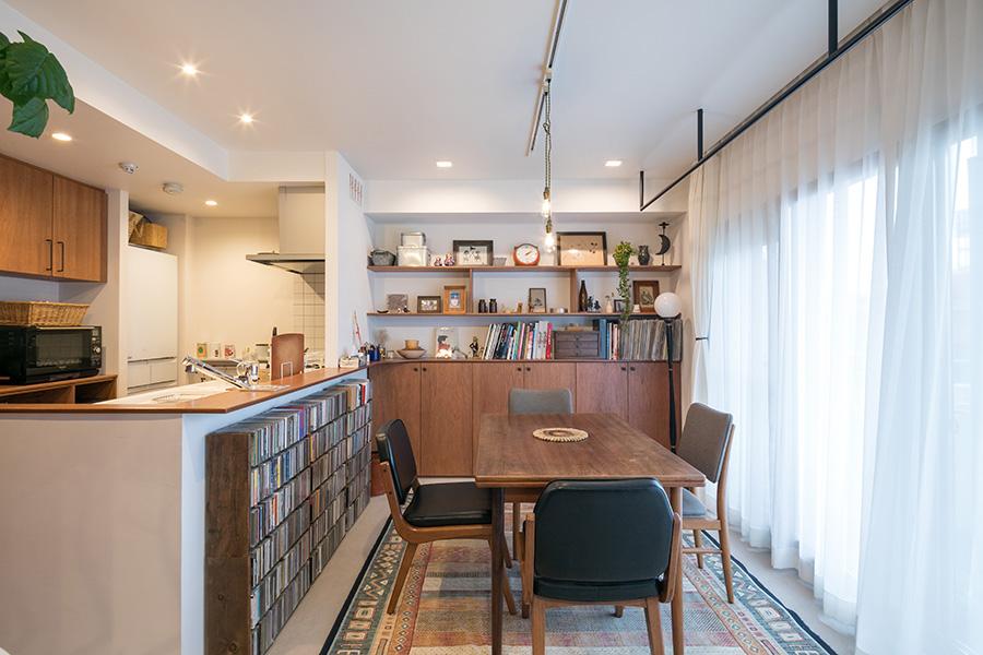 併設したワークスペースからダイニング・キッチンを見る。キッチンから壁面の造作収納まで続くカウンターが、空間に一体感をもたらす。カウンター下のCDラックは以前から使っていたもの。中央のダイニングテーブルは、造り付け家具のモチーフとなったお気に入り。ダイニングチェアはACME Furnitureで購入。