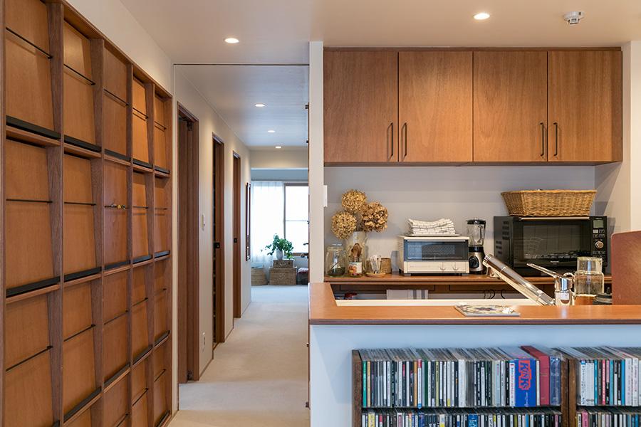 ダイニングから廊下ごしに突き当たりのリビングを見る。左手の書棚の先のドアは、長女の部屋、ウォークインクローゼット、長男の部屋に続く。キッチンや洗面所など水回り以外は、床全面にカーペットを敷いた。