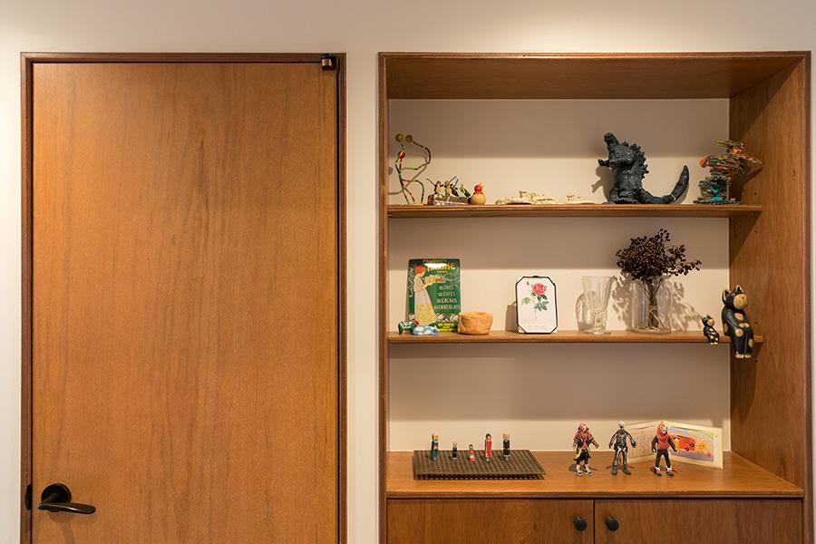 左手は洗面所のドア。建具にもラワン積層合板を用いることでイメージを統一している。廊下に設けた飾り棚は、子どもたちの作品を飾るスペースとして活用。