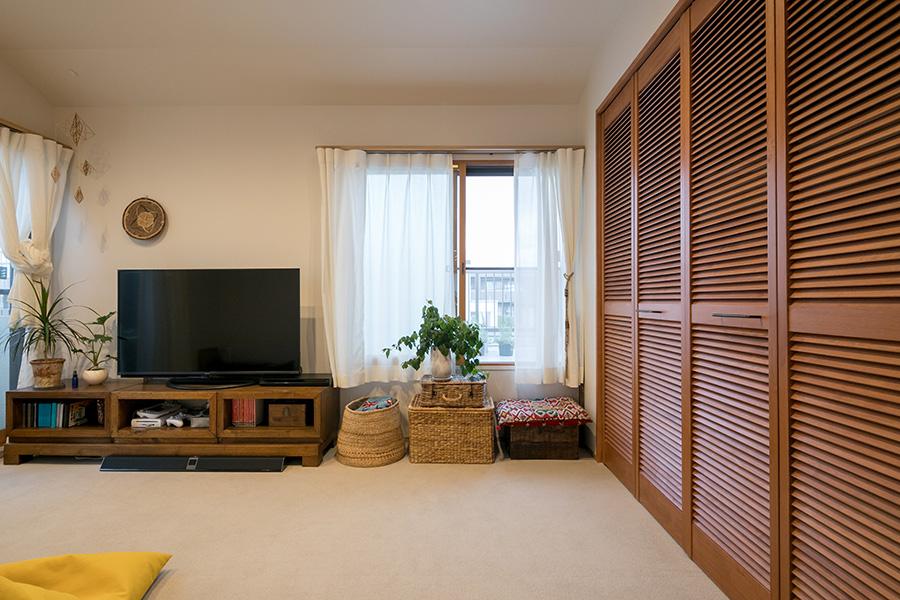 2面開口で風通しの良いリビングルームは、夫の寝室を兼ねる。奥の窓の外にはルーフバルコニーが広がる。