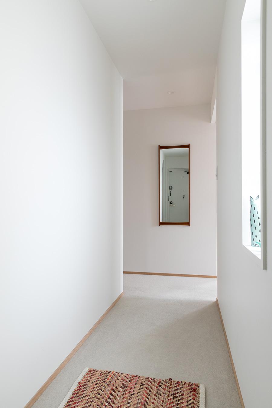 """玄関ホール。右手にある窓のおかげで閉塞感がない。つきあたりの壁掛け鏡は、フレームにチーク材を使った、フィンランド""""Kuvastin Spegel""""社のもの。1960年代のヴィンテージ。"""