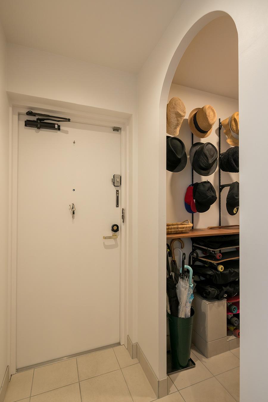 玄関ドアは、空間に調和するように内側を白く塗った。右手のアールの下り壁の中はシューズインクローゼット。家族全員の帽子、靴、スケートボードを収める。