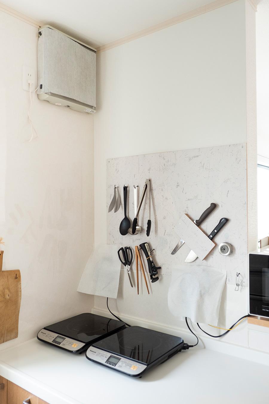 ビルトインの代わりに卓上コンロを選択。使わないときは片づけておけば、広々とした作業スペースが確保できる。レンジフードは換気扇に代えたことで掃除の手間が減り、見た目もシンプルになった。