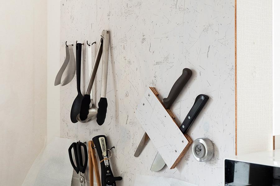 DIYで取り付けたボードに調理器具を収納。片手でさっと取り出したい包丁は、斜めに収められるように工夫している。