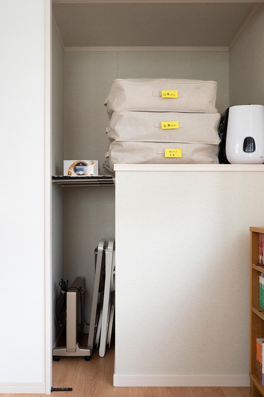 押し入れの扉も外して使用。季節外の家電を収めたスペースの上には突っ張り棒で棚板を渡し、軽めのものを載せている。布団などは無印良品の収納ケースに入れ、分りにくい場合のみラベリング。