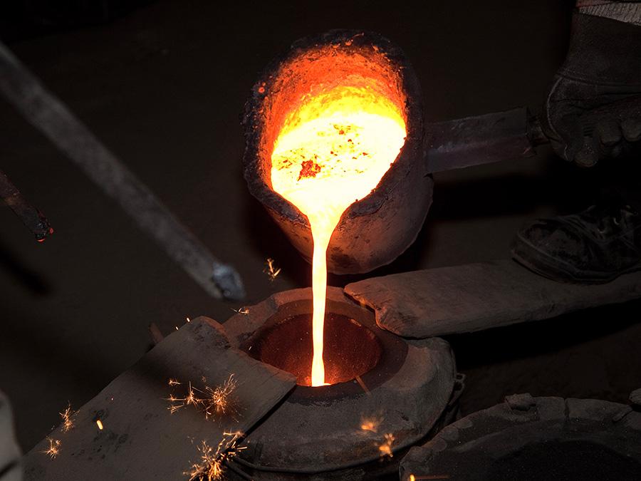 流し込みは数人で行われる。1500度近くの高温で溶かした鉄を狭い注ぎ口の鋳型に注入。