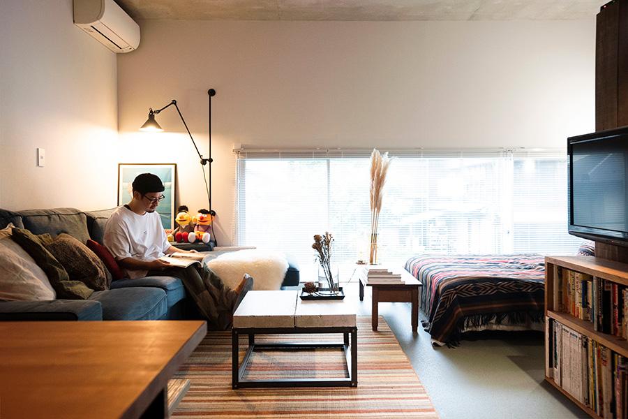 仕切りのないワンルームをDIYでアレンジ。横長の長方形に切り取られた、高さを抑えた窓から光が差し込む。