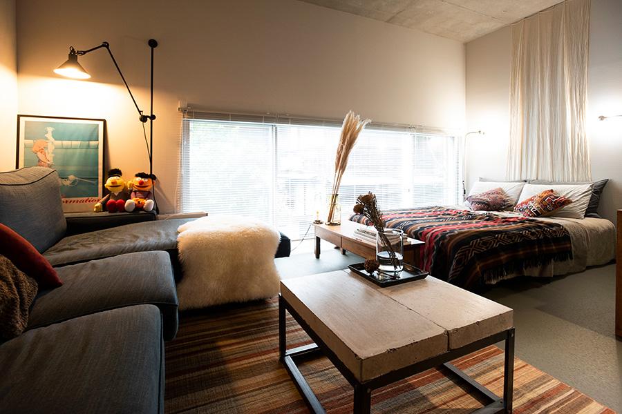 大きなソファーやベッドを置いたスペース。grasのウォールランプでインダストリアル感をプラス。
