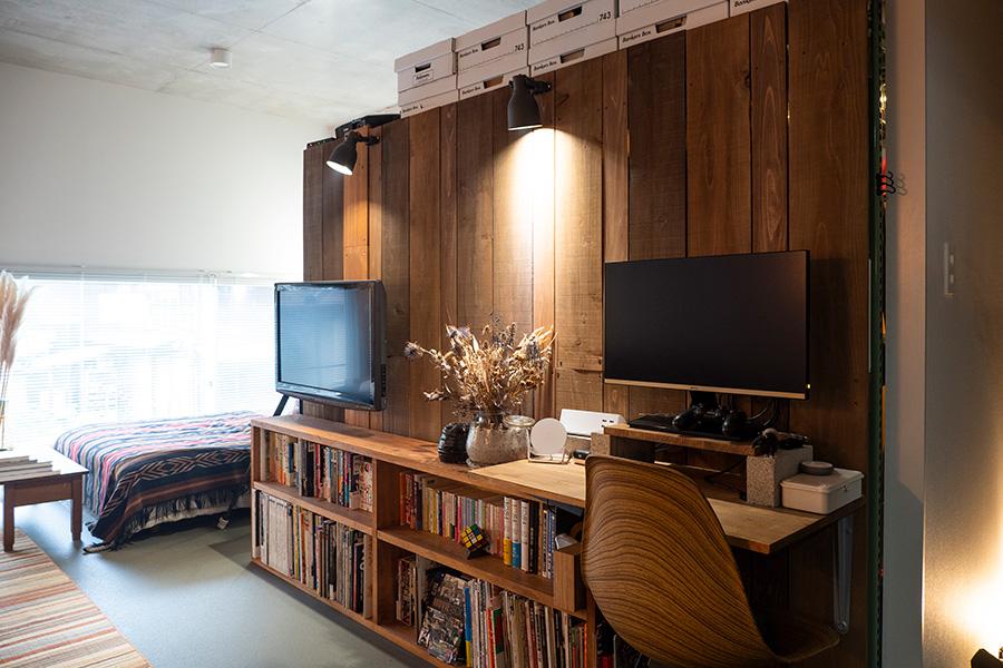 クローゼットを仕切るために設置した木の壁。バラバラの板をランダムに張り合わせている。テレビも首が振れるように、壁に取り付けた。