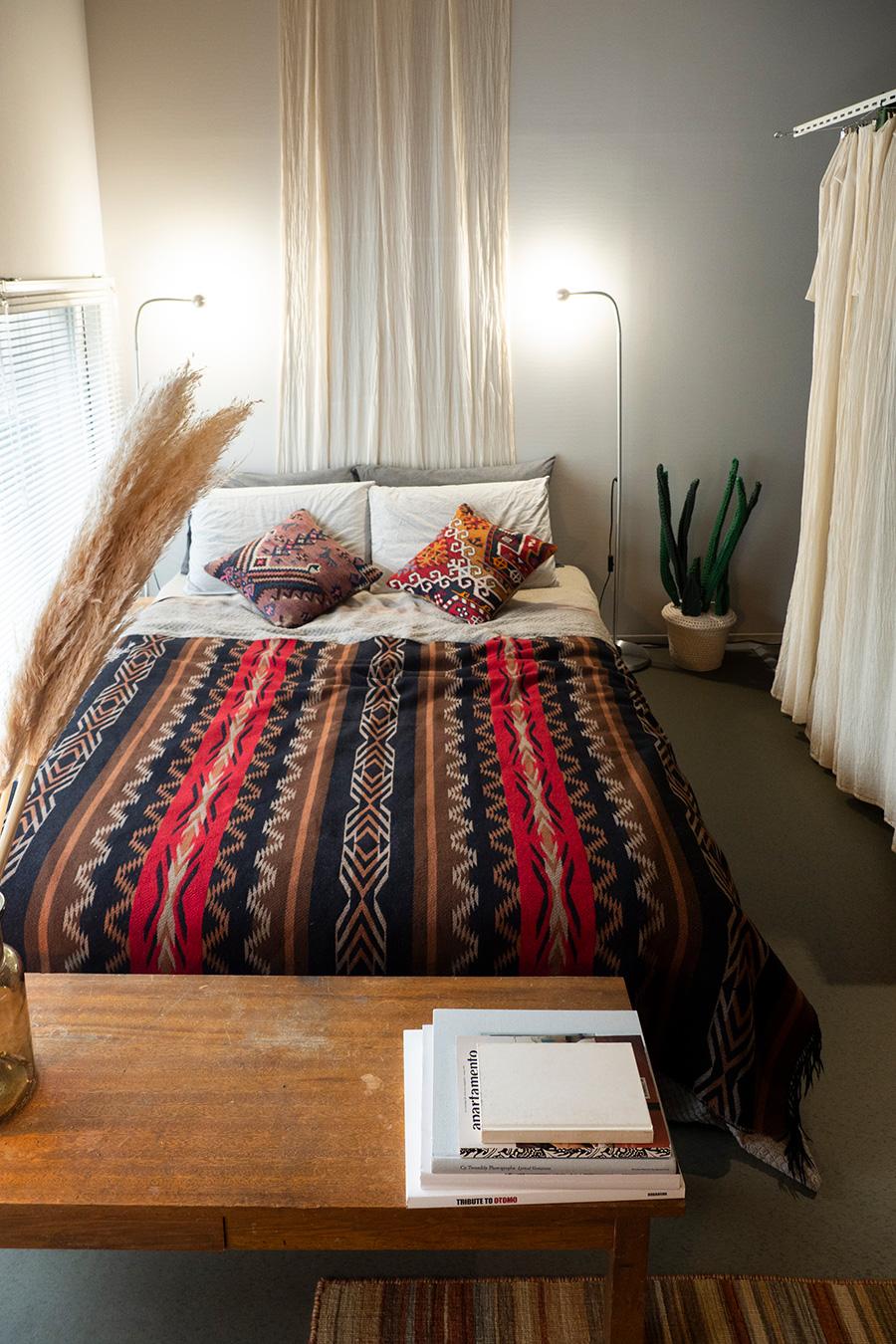 シンメトリーにこだわったベッドまわり。IKEAのスタンドライトはシェードを外して、ランプの光を壁に当てている。ベッドカバーはPENDLETON。