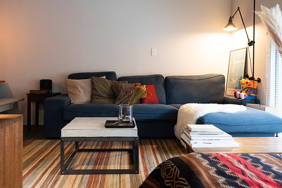 IKEA のソファーがどんと構えるリビング。無機質な空間にファブリックで色を足している。