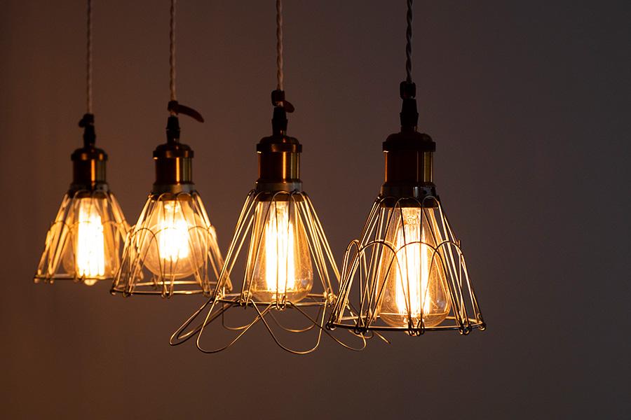 白いコードに真鍮、電球ガードを組み合わせたライト。ワンポイントで皮をあしらった。
