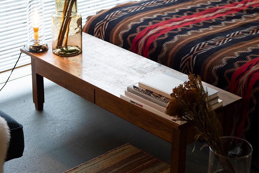 ベッドの足もとの文机が、緩やかな空間の仕切りに。実家から調達したもの。