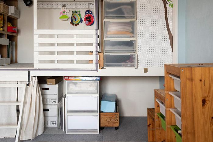 手作りのカーテンで目隠し。白く塗装したハシゴで上がるスペースには、カードゲームなどお子さんの細かなおもちゃを整然と収納している。