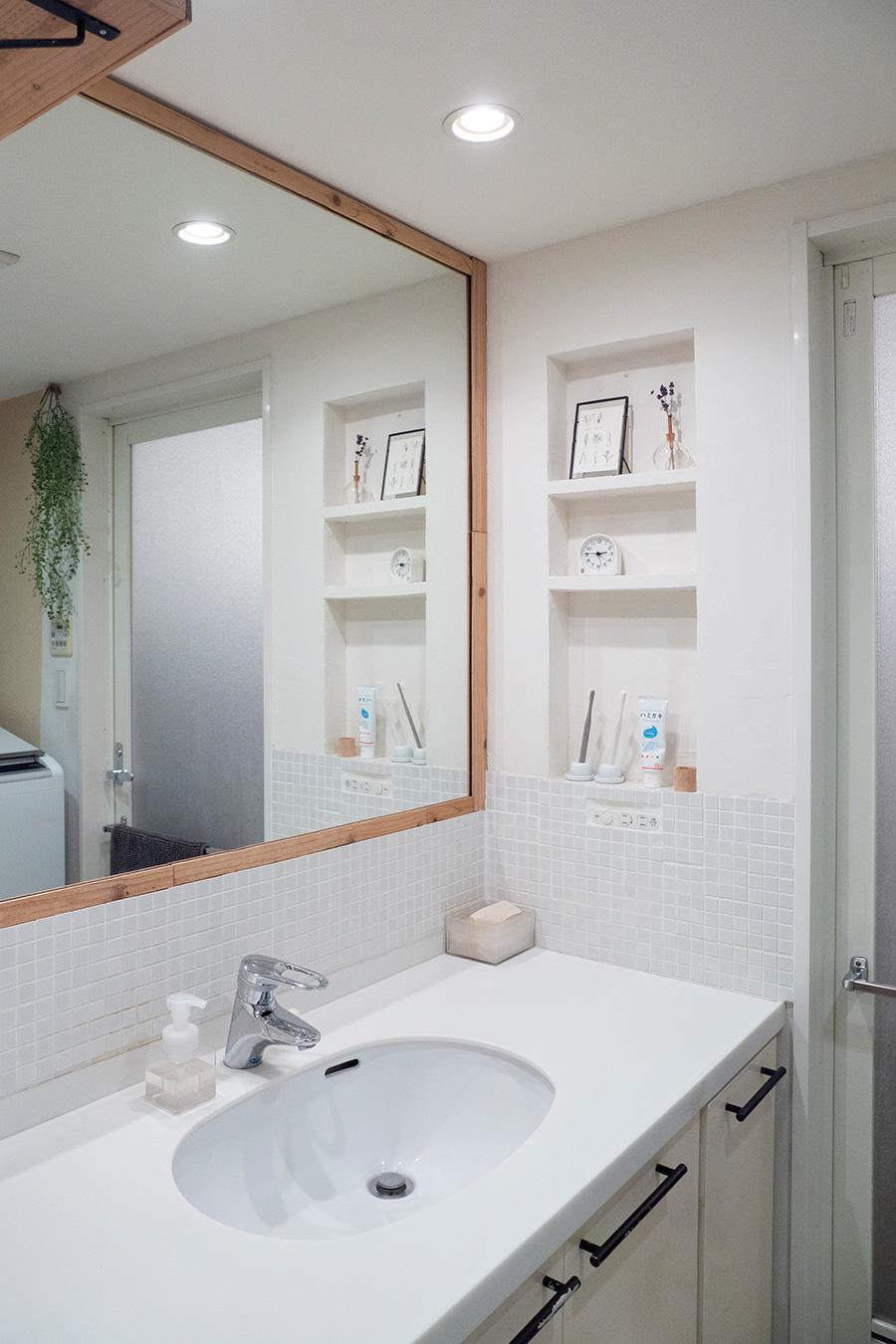 タイルを貼り、鏡のまわりには木の枠を取り付け、壁付け収納は外してニッチに。