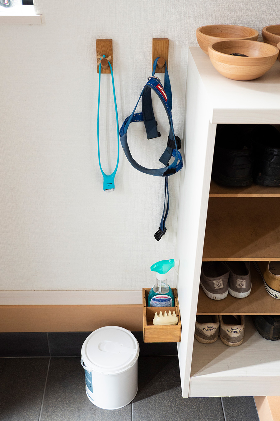 フックにかけたリードは、絡みにくいのもポイント。お手入れグッズも、靴箱に収納を取り付けて、浮かせてスタンバイ。