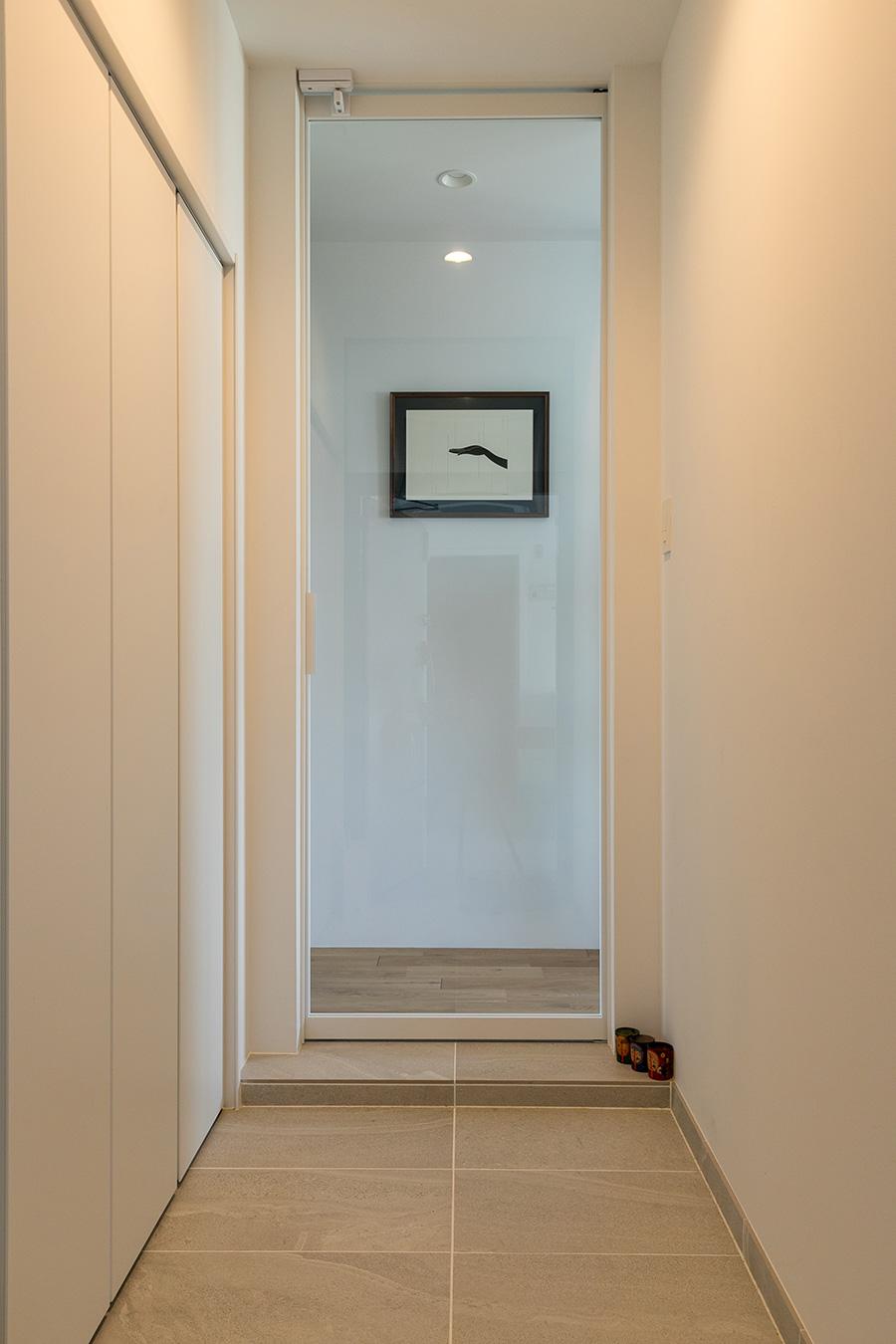 子どもと帰ってきた時や、たくさんの来客時に対応できるよう、玄関のたたきを伸ばして広くした。正面に飾られたグラフィックデザイナーの小林一毅による作品がリビングを指す。