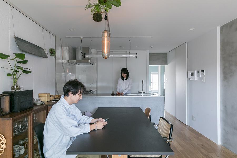 白壁の空間に、所々モルタルがアクセントになり、シンプルながら飽きさせない。正面奥に見えるインパクト社製のキッチンの背面もモルタルで存在感がある。リビングにはartekのテーブル。
