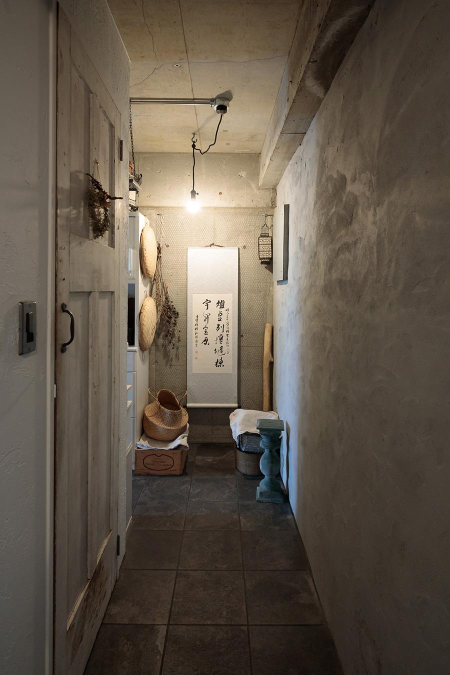 中国の掛け軸をかけた壁は、鉄線の網をかけ、東アジア風の情緒あふれる一角を演出。