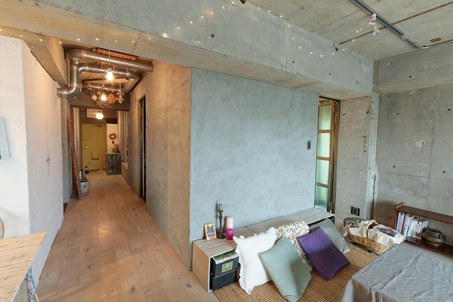 廊下をはさんで左がキッチン、右にバスルームがある。両方を回遊することができる。モルタルと白い壁、それぞれテクスチャーを感じる仕上げにしている。