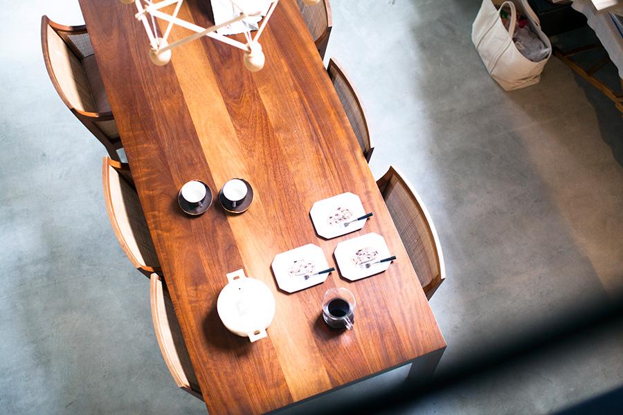 硬質なモルタルの床に、愛用する家具や器が温もりを添える。ダイニングテーブルとチェアはプロダクトデザイナー松岡智之さんのデザイン。