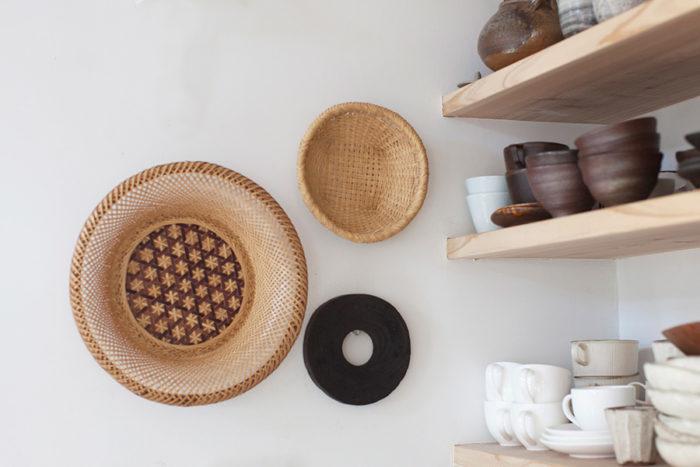 棚板の端は壁に埋め込みしっかりと取り付けている。手仕事の技が伝わるザルや鍋敷を壁に掛けて。