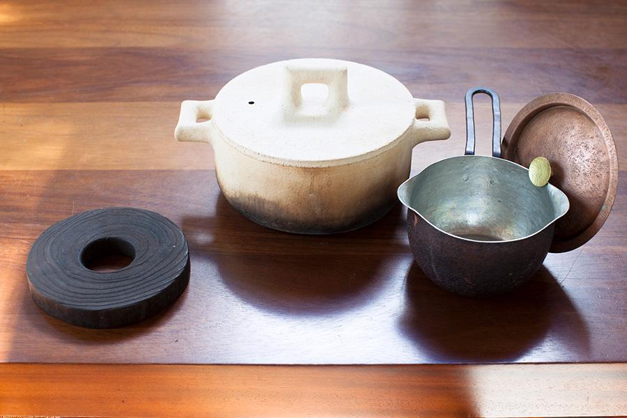左は、金沢の伝統的な桐工芸品をつくり続ける、岩本清商店の桐の鍋敷。美しい木目がお気に入り。素朴な白い土鍋は、伊豆の山中に暮らす陶芸家・渡辺隆之さんの作品。右は鎌倉・WATOの銅鍋。鍋にフタがかけられるのが便利。使い込んだ本体は深みのある色に変色している。