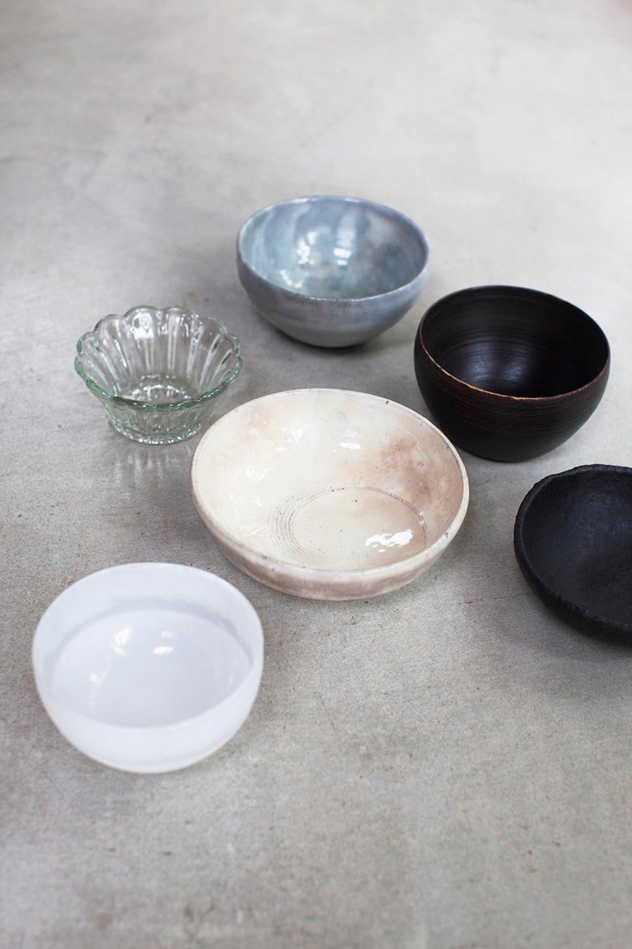 左側のガラスの器は吹きガラス作家アキノヨーコさん(手前)と佐藤玲朗さん(奥)、中央の陶器の器は北九州門司で活動する濱田正明さん。その後ろの茶碗は奈良に青蛾窯を構える松元洋一さん、右手前の陶器に漆をかけた黒いお皿は渡辺隆之さん。奥のお椀は能登の塗師・赤木明登さんの作品。