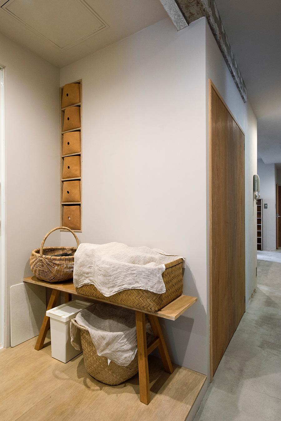 壁の収納の引出しは、hue leatherにオーダーしたもの。やわらかな質感と色合いの革を選んだ。生活用品はカゴに入れて布でカバー。