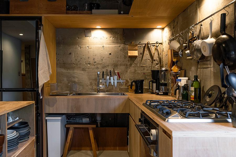 キッチンはシンプルで使い勝手の良いものを目指した。コンクリートの荒々しさを素朴なラワンの雰囲気が和らげる。コンロ、シンクを指定し、収納の使い勝手を考えてオーダー。