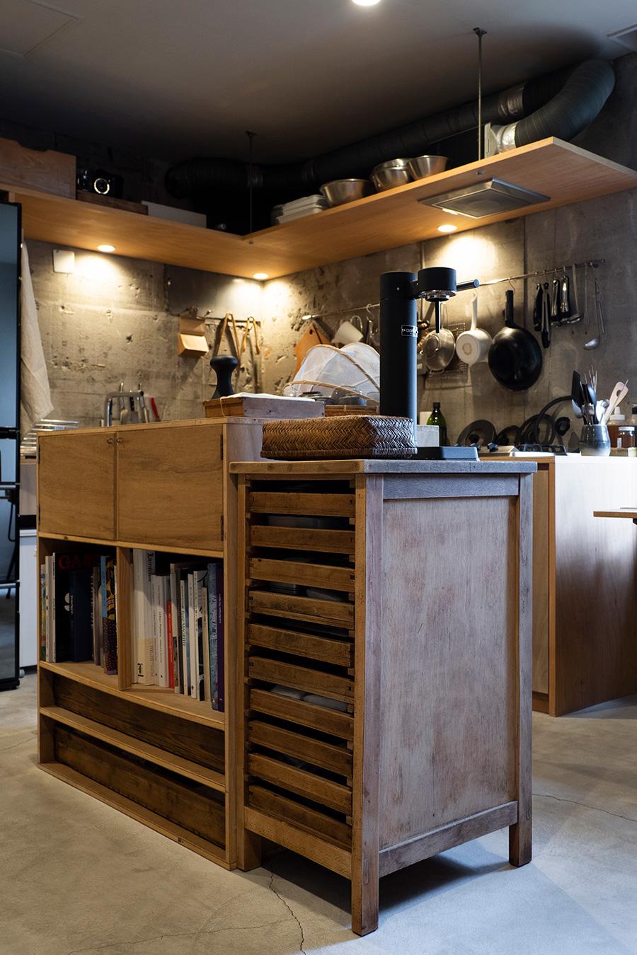 中央の造作の棚の隣には、古道具の棚をコーディネート。本や食品、ストック食材をアイランドに収納。