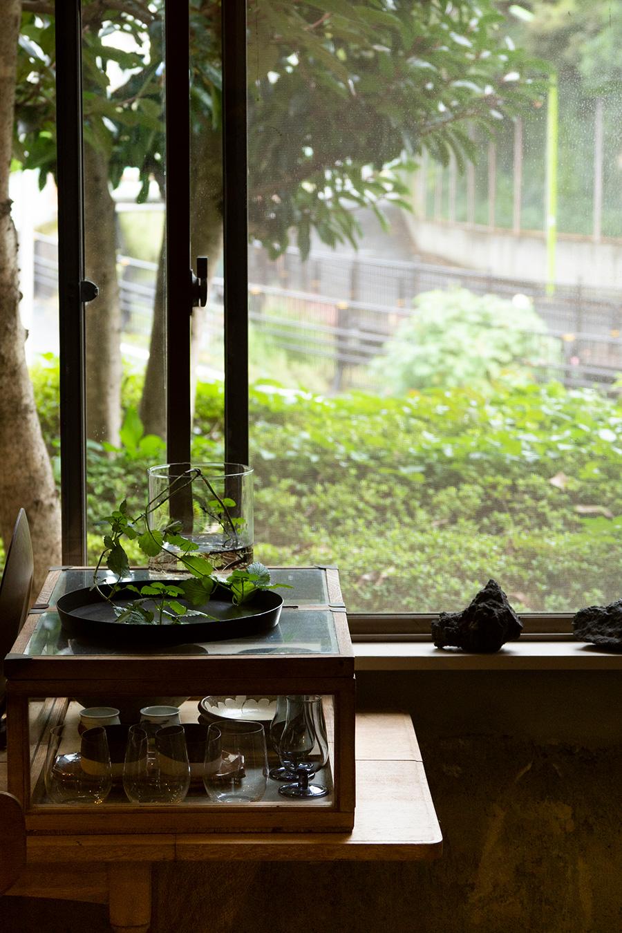 キッチンからも通りの緑が眺められる。古道具の什器にお気に入りの作家さんの作品を飾る。