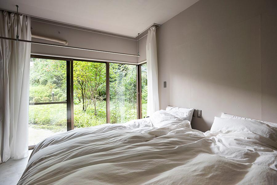 森の中の別荘にいるようなベッドルーム。ベッドの高さを抑えることで天井高を確保している。