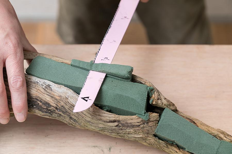 穴の開いた朽木にオアシスを詰める。余分はカットしながら、端材を溝に差し込んでなるべく隙間なく埋め、全体を指でならしていく。