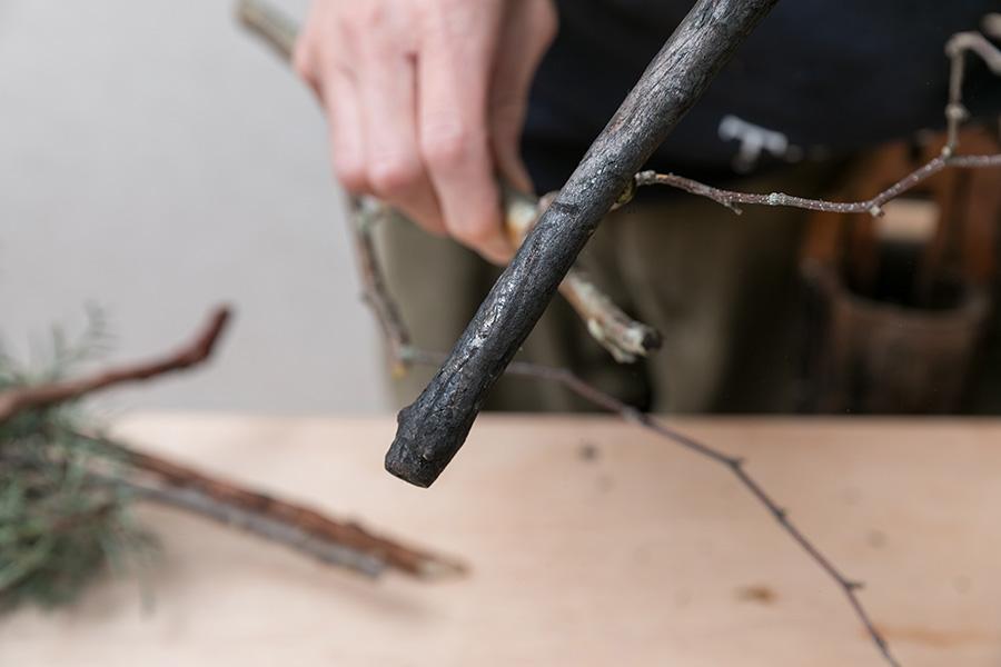 「枝をカットして使いたい形に整えた際、切り口が白く浮いてしまいます。そんな時は炭を切り口に塗りつけて時間が経過した自然な切り口に見せます」