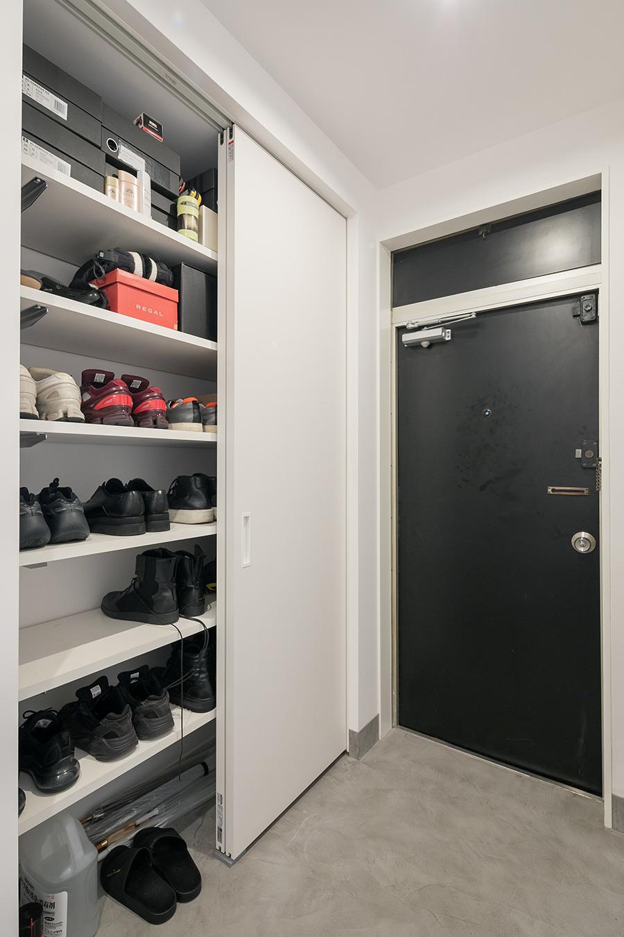 本棚の壁向こうには玄関収納スペースを設置。