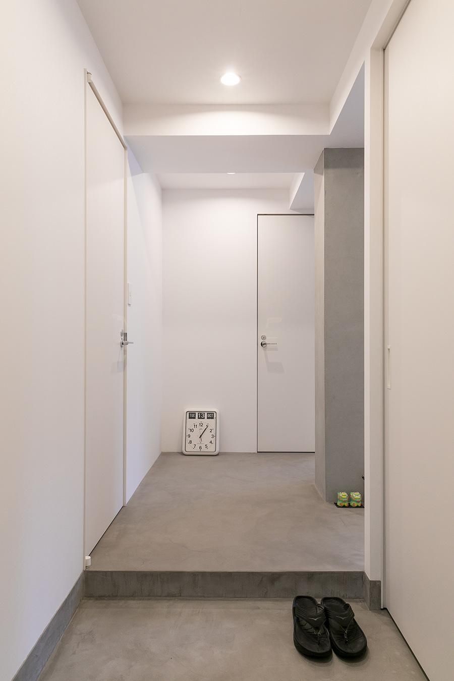 玄関から延びる廊下。右側のモルタル躯体前の壁を無くし空間を広くした。