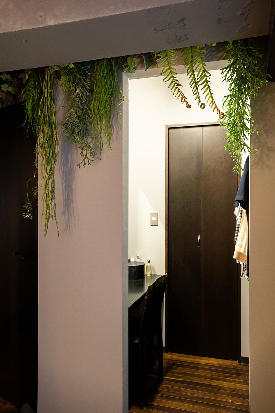天井の梁を利用してフェイクグリーンをベッドから見える場所へ。その奥はドレッシングルーム。大容量のウォークインクローゼットは扉の奥に備え、生活感を出さない工夫を凝らしている。