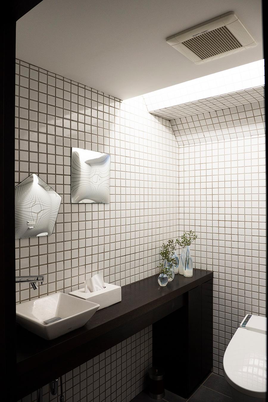 タイル張りのトイレも広々と設定。壁の鏡はTsé&Tsé associéesの「うそつきの鏡ペンタゴン」。変顔しか映らない、遊び心とアート感のあるこのミラーがお気に入り。