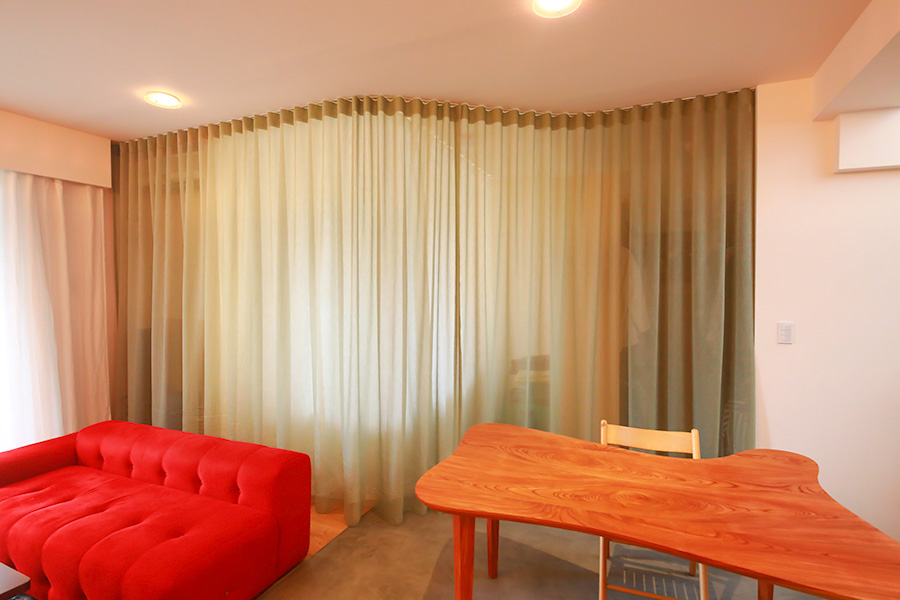 天井が高い空間の良さを活かし、天井から床までの長さがあるカーテンでワンルームを柔らかく仕切っている。カーテンの向こうがベッドルーム。夫婦でデザインしたケヤキ材のオリジナルのダイニングテーブルも柔らかな曲線を描く。