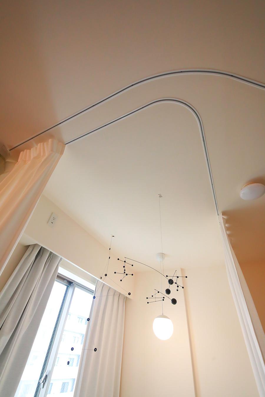 S字とL字、2本のレールが天井を走る。サイレントグリス社のレール「WAVE」は、カーテンのドレープが均等になる機能を持つ。